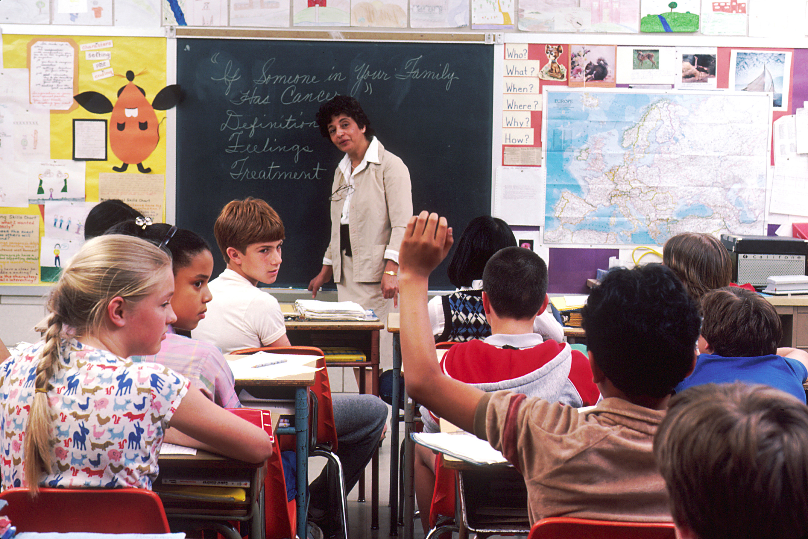 Image of children in a traditional classroom facing the front in desk and chairs with one boy raising hand and teacher looking at him.