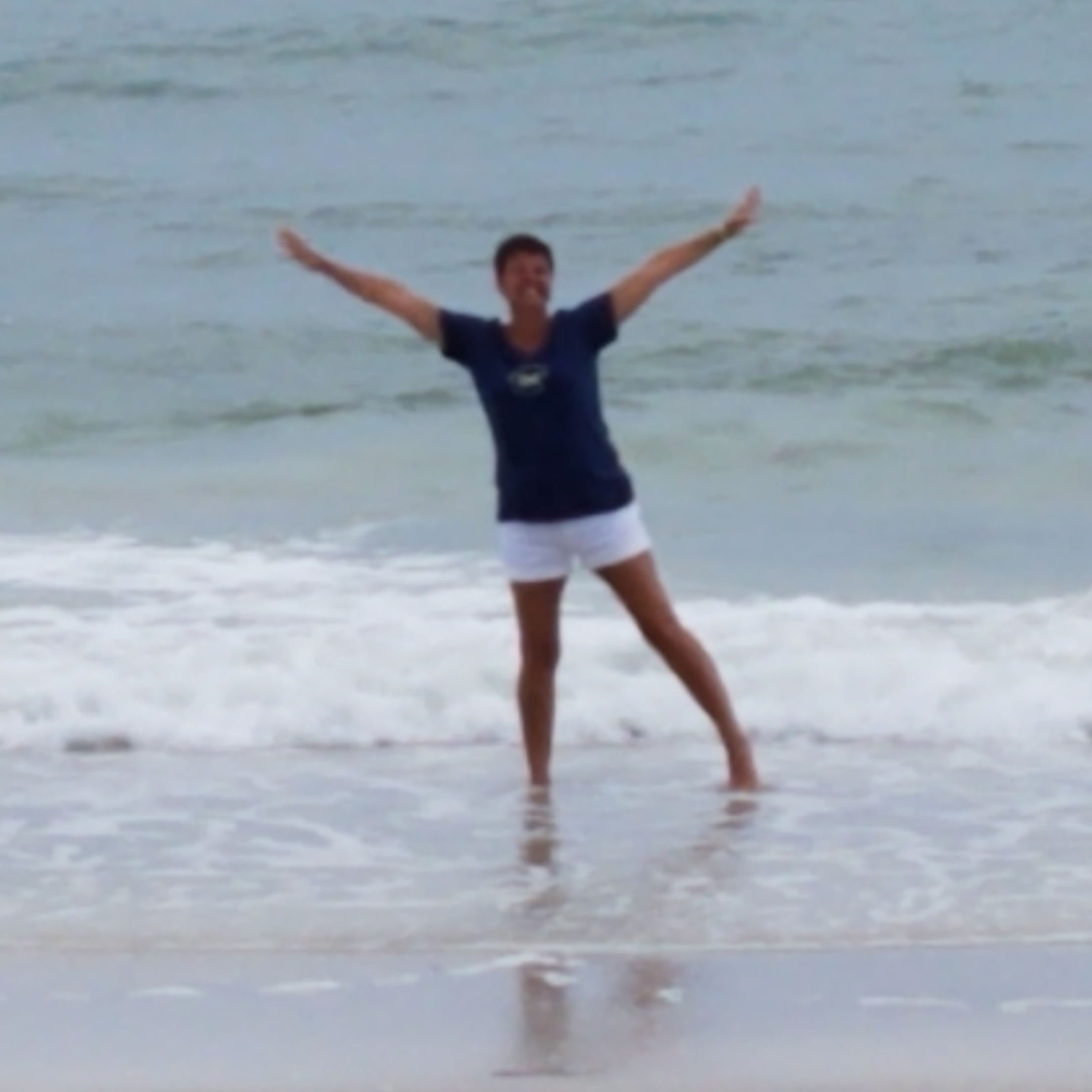 Sandi Smith standing on the beach with arms open like a Y and legs spread apart