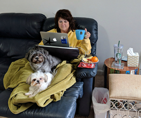Sandi is sitting on her couch with a blanket over her and two dogs on her legs. She is typing on her computer and has her sick table materials beside her.