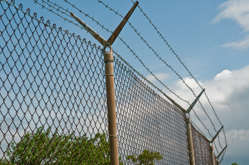 image of barrier, barbed-wire fence around a field
