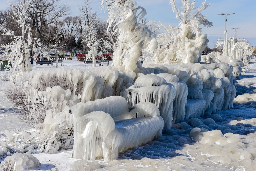 bench and bushes in a park near Lake Michigan covered in ice.
