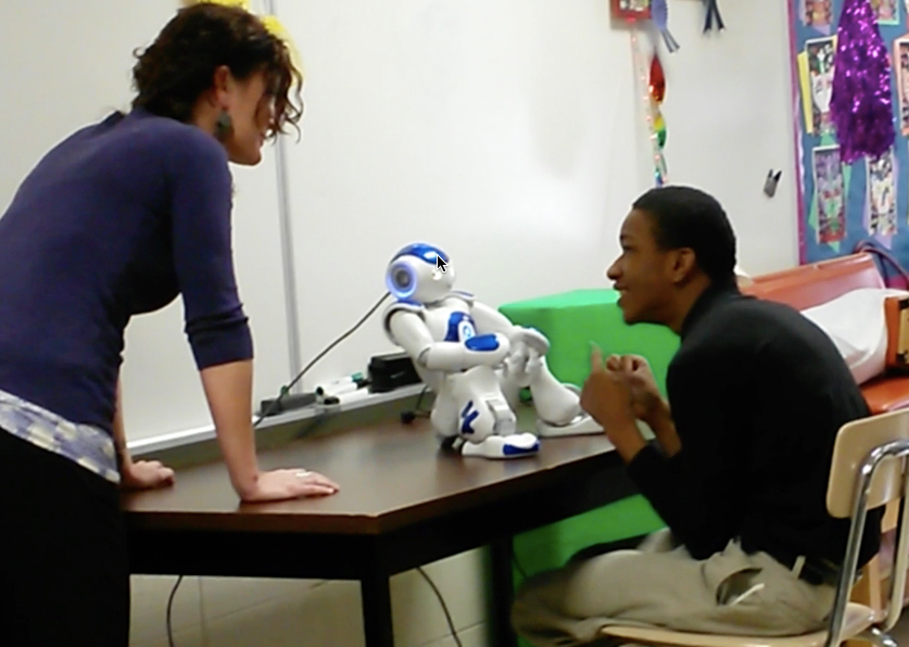 Kelli working with Ophi, the robot, and a student