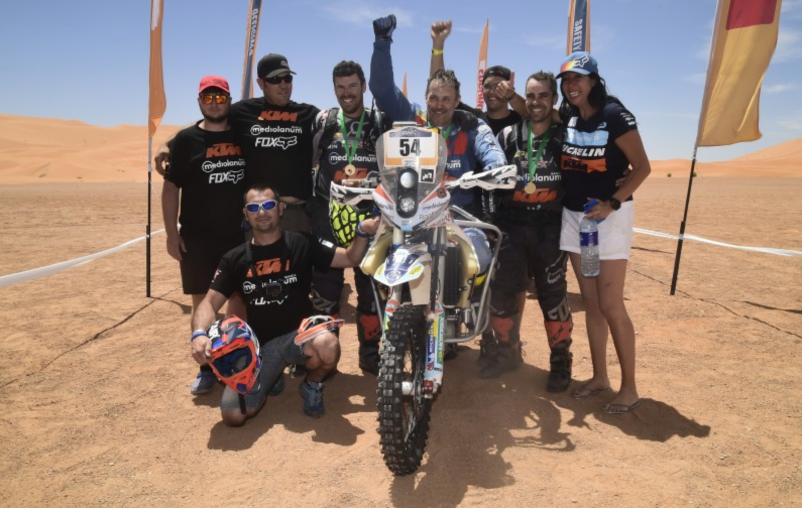 Nicola Dutto and his team after a race, with him sitting on his motorcycle accommodated to allow him to race as a paraplegic.