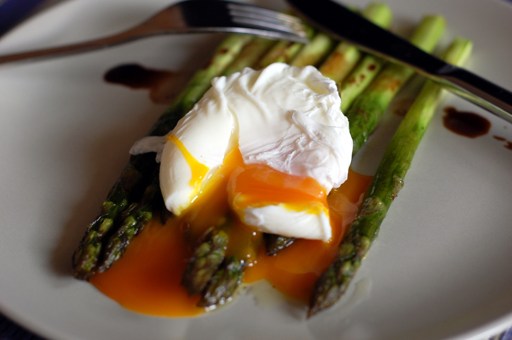 photograph of a runny poached egg atop cooked whole asparagus with a fork and knife in the background.