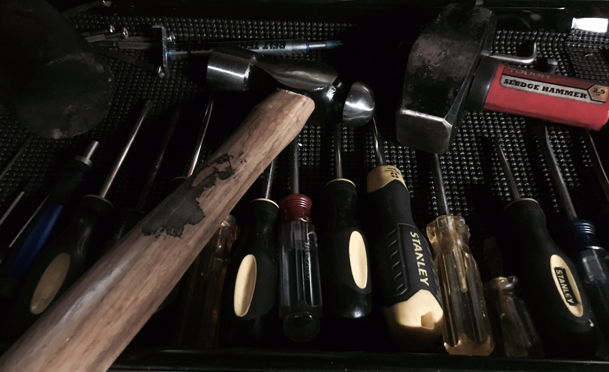 A picture of 3 hammers and multiple screwdrivers in a tool drawer