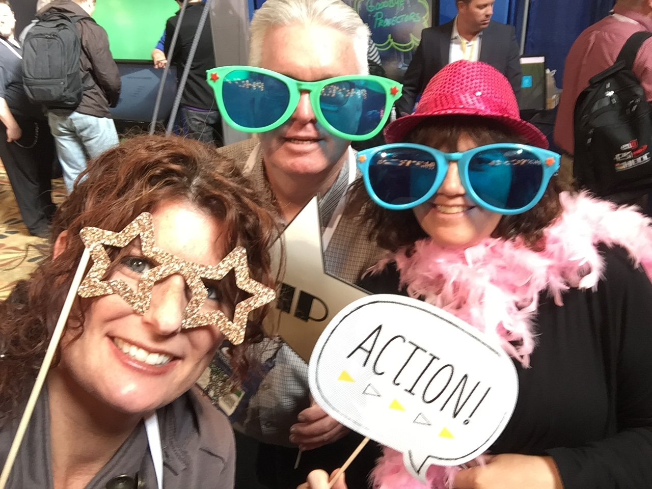 Kelli Suding, Jim Lambert, and Sandy Stabenfeldt posing with photo booth props