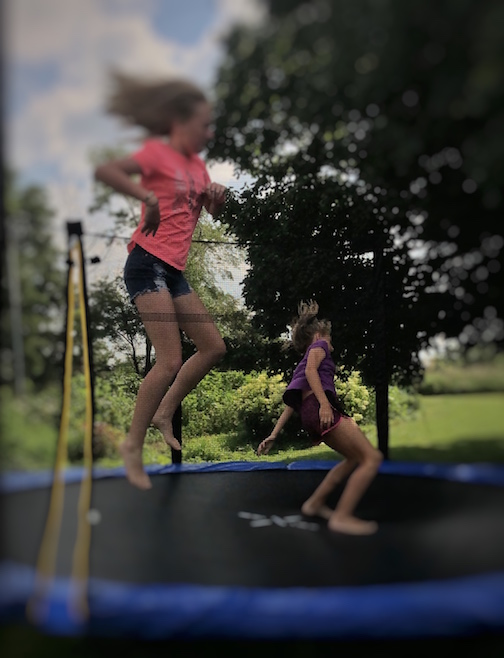 two teen girls jumping on a trampoline at the Sharritt's farm