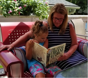 Kenzi reading to Mimi on the glider outdoors.