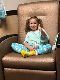 Kenzie setting in a chair giving a thumbs up.
