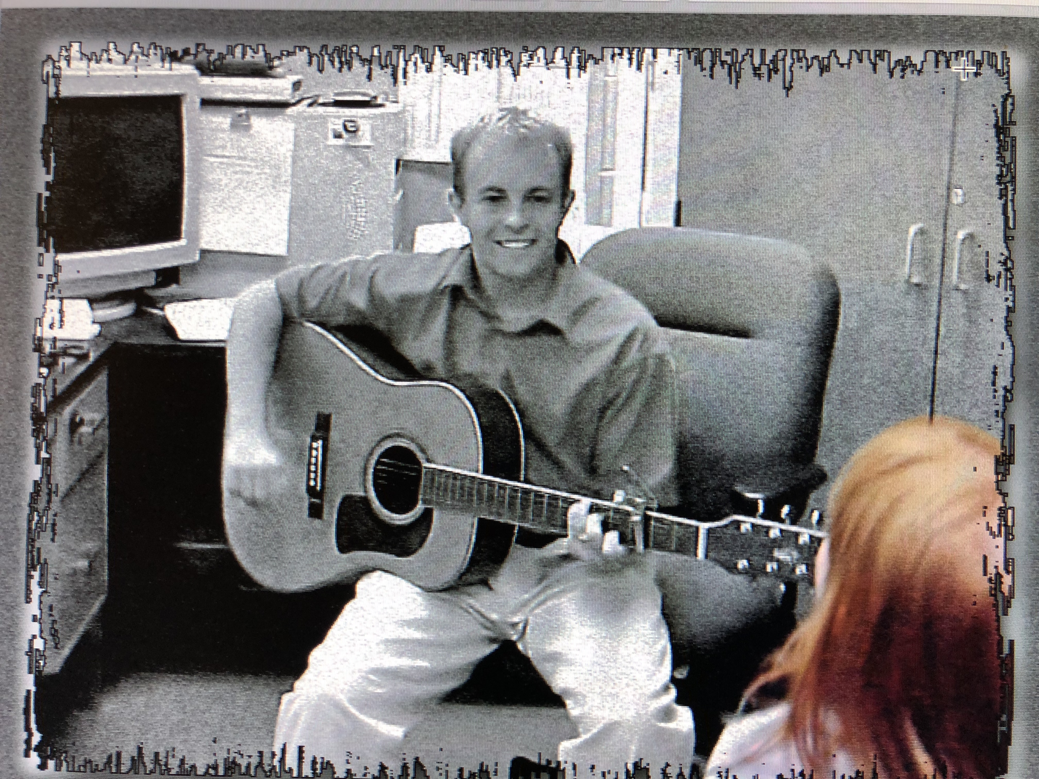 Daniel as a first year teacher playing guitar for students.