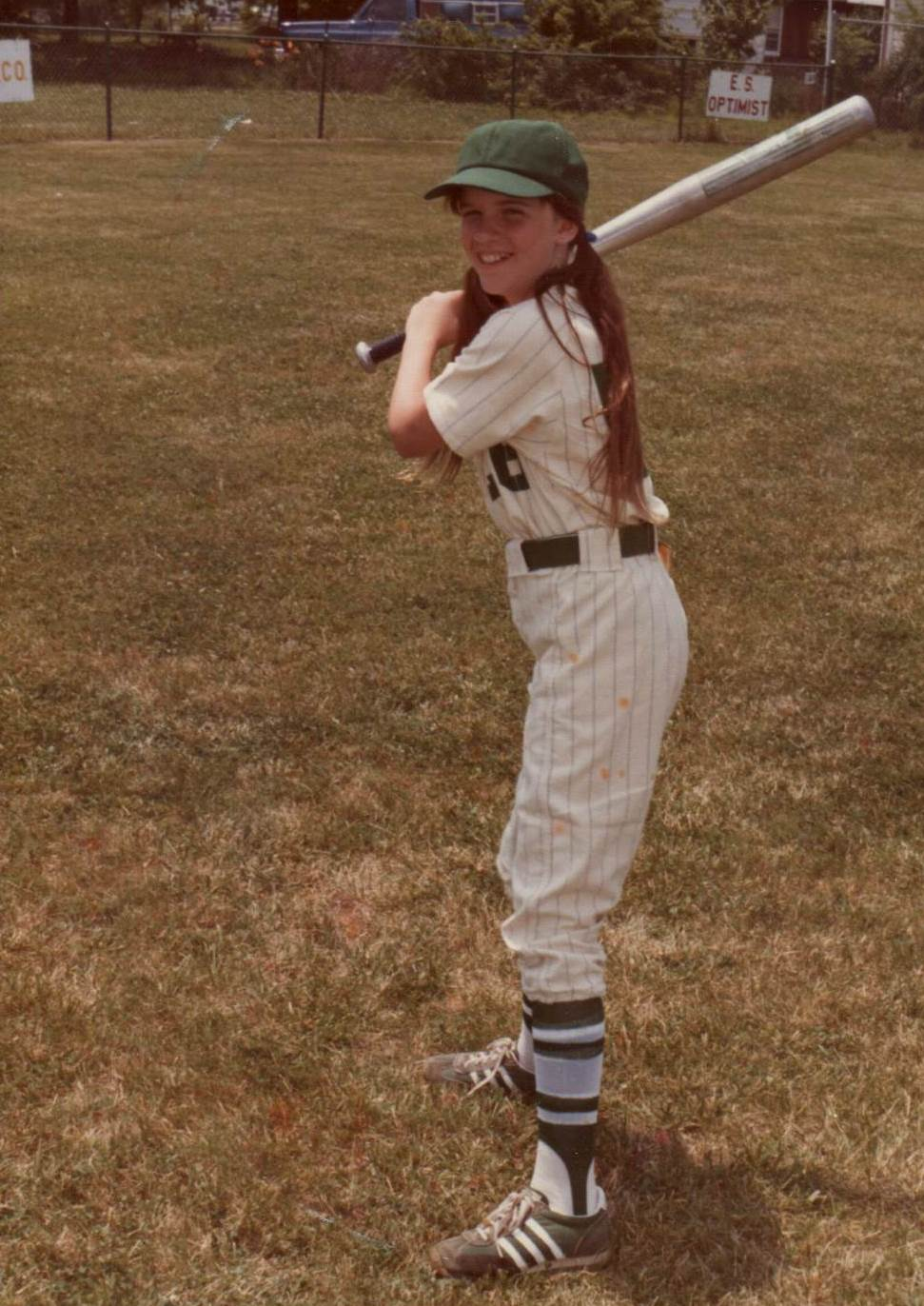 Sandy as a young girl in her baseball uniform.