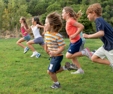 5 elementary aged students running through the grass