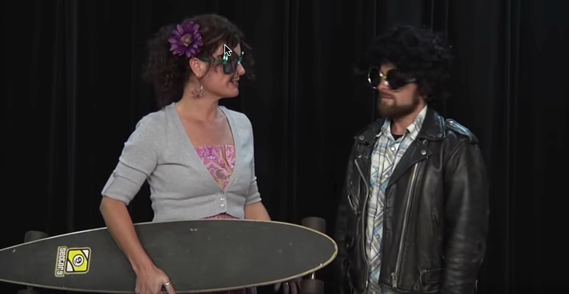 Kelli Suding holds a long skateboard and Daniel McNulty