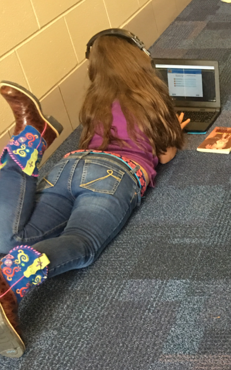 female 3rd grader using a laptop and headphones while laying on the floor