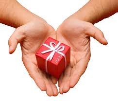 Hands holding a small red gift with white ribbon.