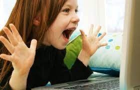 excited preschool girl with open hands raised near her face looking at device screen