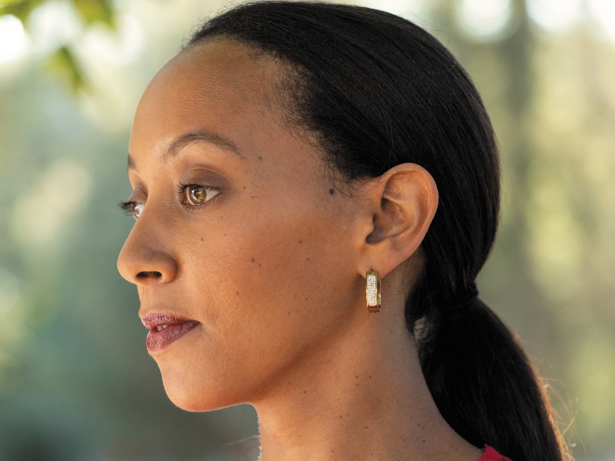 Haben Girma, a woman with light brown skin looks into the distance. Her dark hair is pulled back and she is wearing small gold earrings.