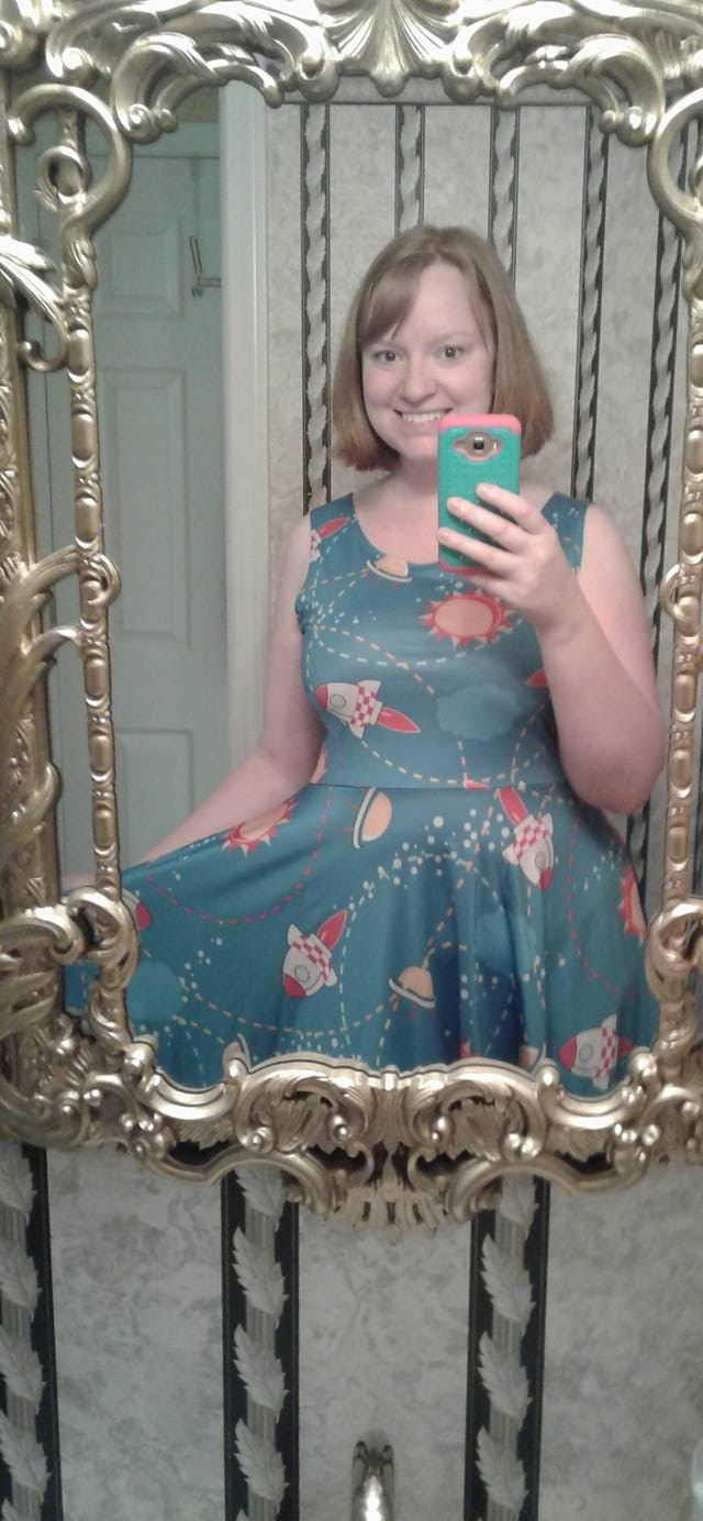Jessica holding her cellphone taking a selfie in a mirror wearing a blue dress with cartoon rocketships