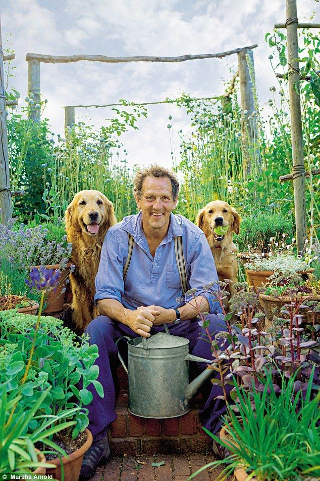 British gardening guru Monty Don holding a watering can in his garden with his 2 golden retrievers at his side