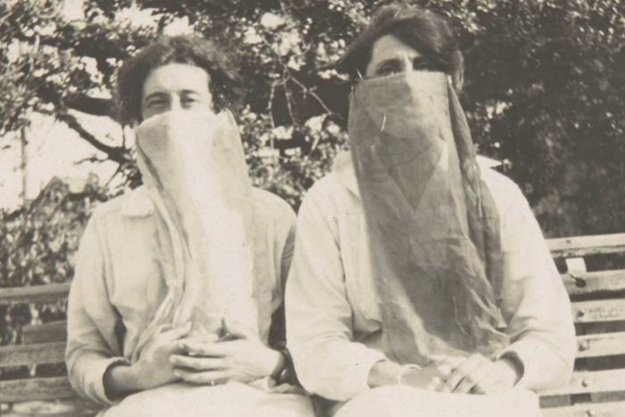 sepia tone photo of two women sitting on a bench wearing cloth masks circa 1918