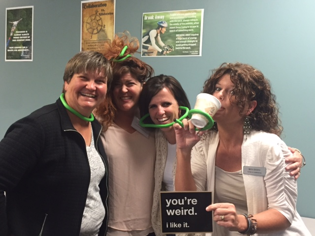 Gloria Crowell, Rachel Herron, Shellie Parr, and Kelli Suding being silly with a sign worded you're weird. I like it.