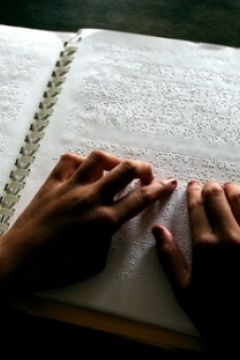 Student reading a braille book